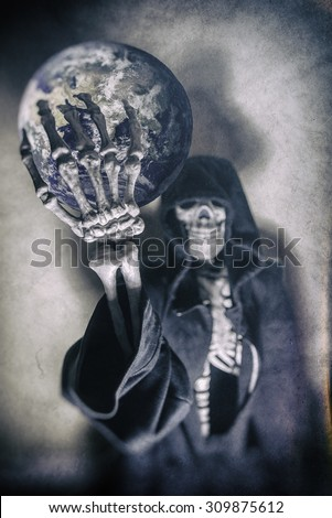 Grim Reaper Holding the Earth. Grim Reaper in hood holding up the Earth. Shot with spot lighting and edited with vintage filters. - stock photo