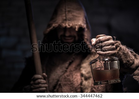Grim Reaper is holding a bottle of alcohol drink. The man is standing and smiling. He is carrying a scythe and laughing - stock photo