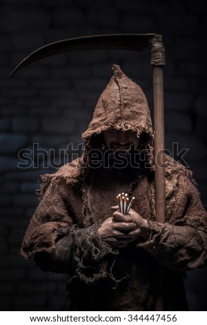 Grim reaper is holding cigarettes and smiling. The man is standing and carrying a scythe. He is wearing a robe - stock photo