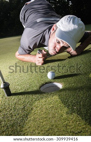 Grimacing golfer lying down on the green, blowing on his white ball to make it fall in the hole. Close up  on the ball and the man head with a beautiful forest in the background. - stock photo