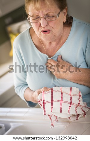 Grimacing Senior Adult Woman At Kitchen Sink With Chest Pains. - stock photo