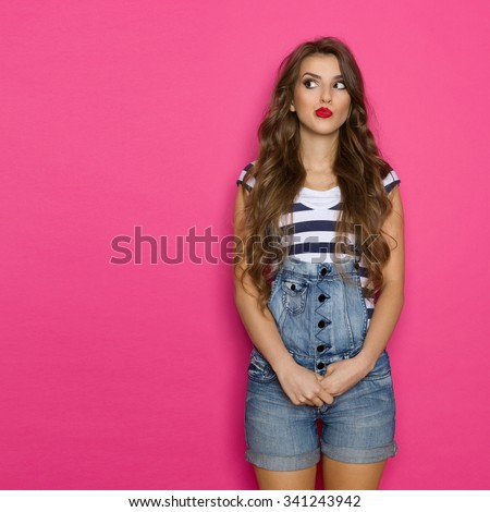 Grimacing young woman in dungarees looking at copy space. Three quarter length studio shot on pink background. - stock photo
