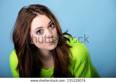 Grimacing young woman making silly face on blue background - stock photo