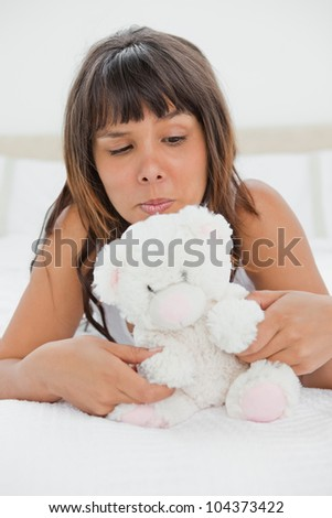 Grimacing young woman playing with a teddy bear on her bed