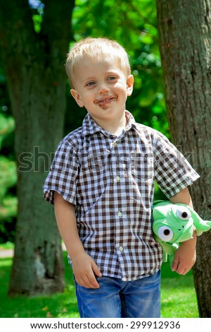 Grimy little boy in park. He is dressed in a plaid shirt and jeans, in a hand holds a soft green toy - stock photo