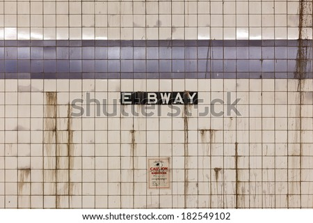 Grimy wall with rat poison warning at East Broadway subway station in the Lower East Side of New York, NY, USA. - stock photo