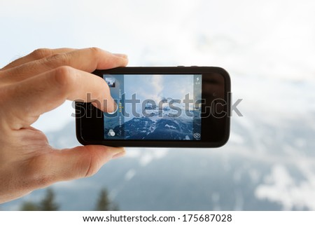 GRINDELWALD, SWITZERLAND - FEBRUARY 4, 2014: Man taking a photo of the Eiger mountain using the camera app on an Apple iPhone 4s. Close-up shot of the hand holding the phone with the mountain behind.