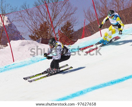 GRINDELWALD, SWITZERLAND-MARCH 10: Athletes fight for lead position at FIS Skicross Worldcup in Grindelwald, SUI on March 10, 2012. Racer Nick Zoricic died, racing into a safety fence at run end.