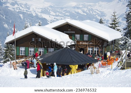 GRINDELWALD, SWITZERLAND �¢?? MARCH 07, 2009: Unidentified tourists relax at the Brandegg ski station in Grindelwald, Bernese Alps, Switzerland. Grindelwald area is a famous ski resort in Switzerland. - stock photo