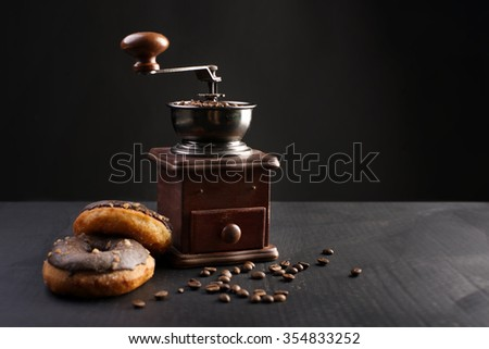 grinder, a donut and coffee spilled on a table