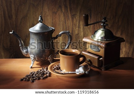 Grinder, coffee pot, brown cup of coffee with beans over wooden background