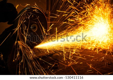 grinder cuts the metal with an abrasive sparks fly