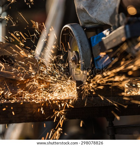 Grinding machine in action with bright sparks. Construction and manufacturing theme. - stock photo