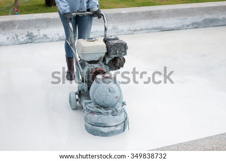Grinding the cement floor  pool machine and construction worker - stock photo