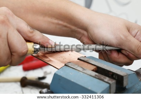 Grinding the copper billet with a file, close up - stock photo