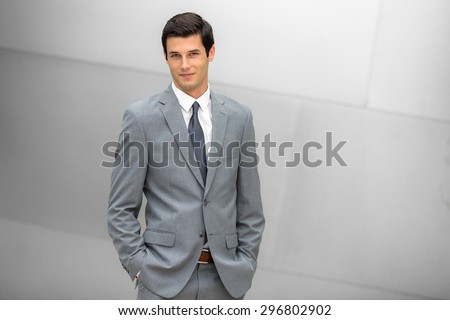 Grinning businessman in a trendy suit young and positive expression at the office modern corporate leader - stock photo