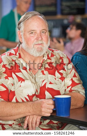 Grinning mature man sitting in cafe with coffee - stock photo