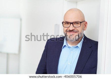 Grinning single smiling business man in blue shirt and blazer leaning against doorway with blank chart and wall - stock photo