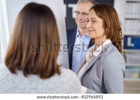 Grinning woman with group of fellow adult business executives meeting together in office - stock photo