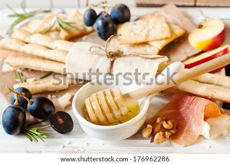 Grissini bread sticks, crackers with salt, rosemary honey, prosciutto ham, apple and grape on a white cooking board close-up. - stock photo
