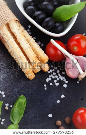 Grissini bread sticks with sesame, sea salt and basil on old black background, top view - stock photo