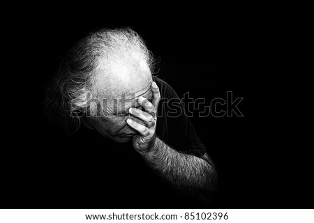 Gritty black and white image of older man holding head in despair, grain added to make more dramatic. - stock photo
