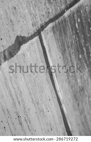 Gritty grey wall of cement forms pattern at joining. - stock photo