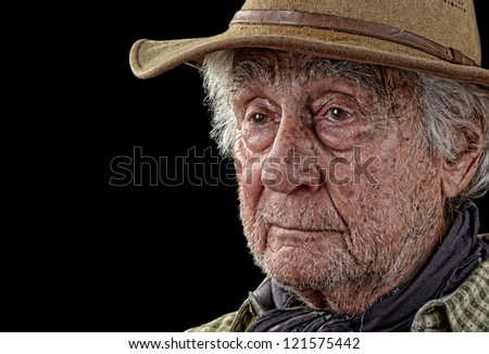 Grizzled old man wearing a tan felt hat looking pensive - stock photo