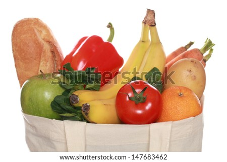 Groceries including a baguette, fruits and vegetables, isolated on white - stock photo
