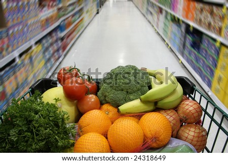 Grocery cart filled with nutritious fruits and vegetables. - stock photo