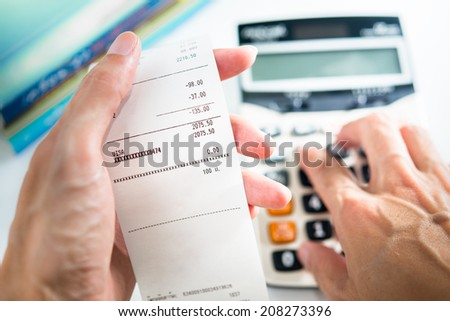 Grocery shopping list in hand with calculator - money account management concept - stock photo