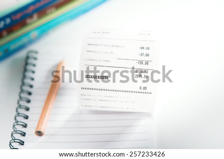 Grocery shopping list on notebook and pencil - money account management concept - stock photo