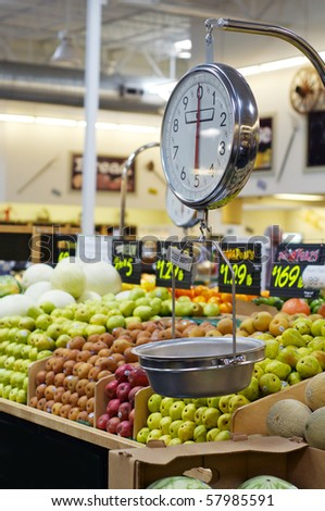 Grocery store scale with fruit and veg in background - stock photo