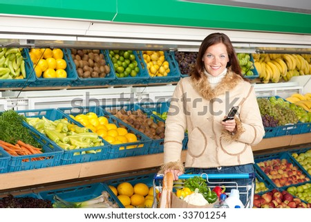 Grocery store - Smiling woman with mobile phone in a supermarket - stock photo