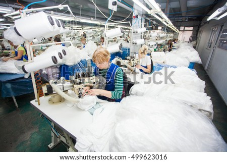 GRODNO, BELARUS - DECEMBER 13, 2013: Seamstress in textile factory sewing with a industrial sewing machine .