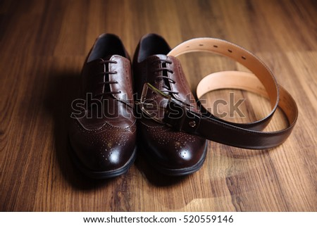 Groom accessories shoes, strap on the table. Concept of gentleman dress
