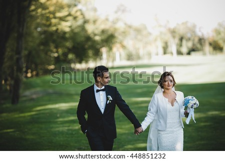 Groom admires a pretty bride holding her hand during a walk