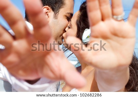 groom and bride cover camera with their hands while kissing - stock photo