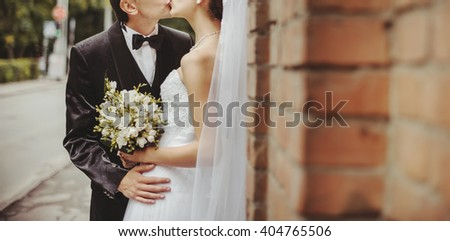 Groom and Bride embracing next to red brick wall. Hands of newlyweds  together. Wedding Couple.