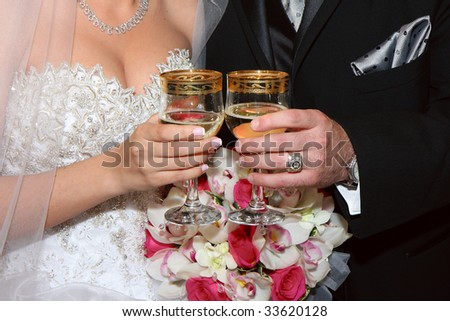 Groom and Bride hold glasses of champagne - stock photo