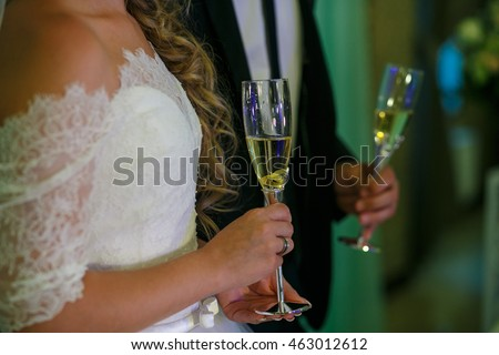 Groom and bride hold the glasses with champagne