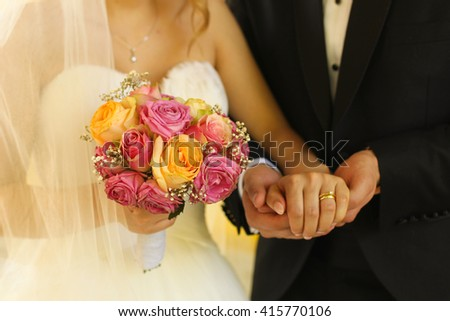 groom and bride holding hands and wedding bouquet