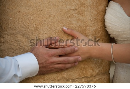Groom and bride holding hands during weding photography session - stock photo