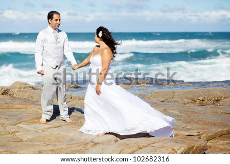 groom and bride holding hands on beach rocks - stock photo