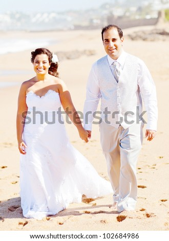 groom and bride holding hands walking on beach - stock photo