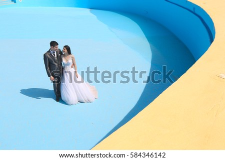 Groom and bride in a empty pool