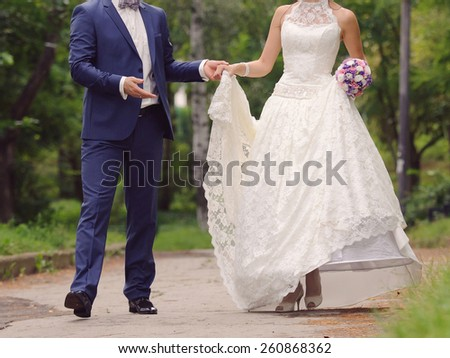 groom and bride in lace dress walking in park - stock photo