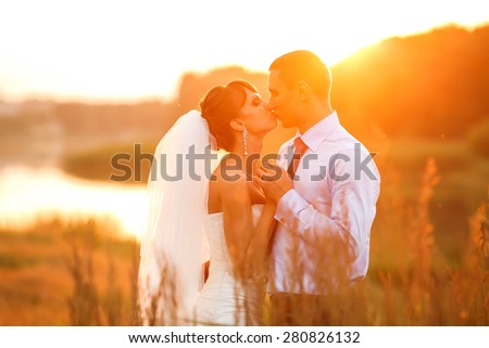 groom  and  bride is hugging and kissing on the background beautiful sunset on the lake - stock photo