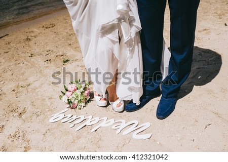 Groom and bride is walking on the bank of river - stock photo