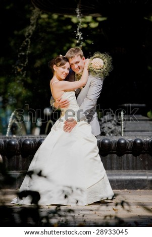 Groom and bride joy against backdrop fountain. In all growth. - stock photo